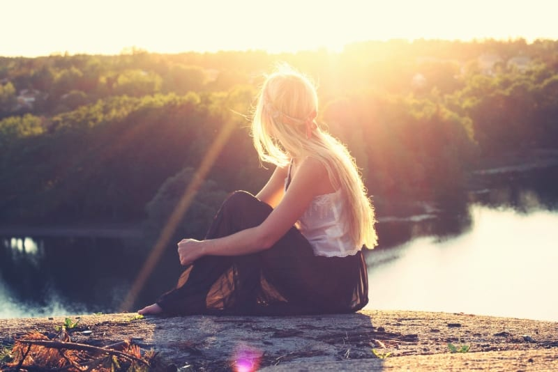 blonde woman sitting on ground looking at water