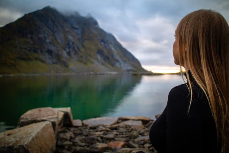 woman in black jacket sitting on rock looking at lake