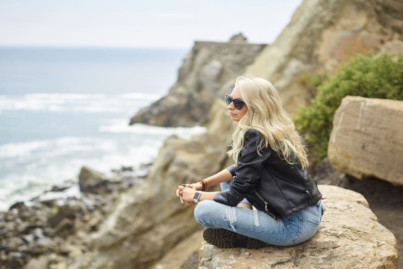 blonde woman with sunglasses sitting on rock