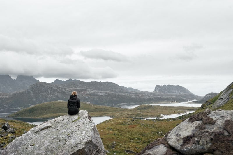 woman sitting on gray rock looking at mountain