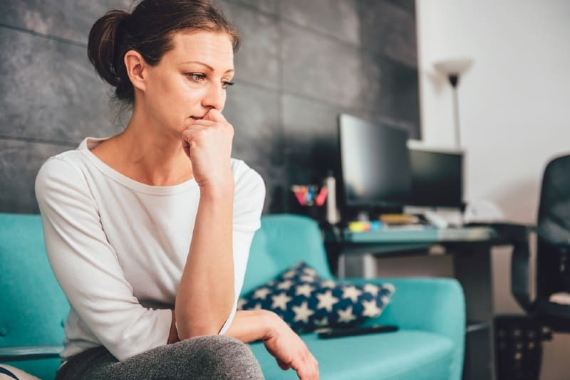 sad woman sitting on sofa in living room