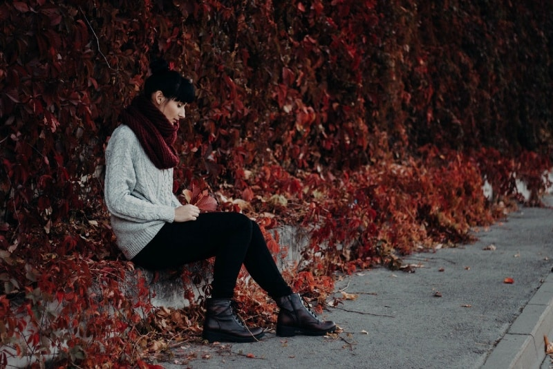 woman with burgundy scarf sitting on the pavement