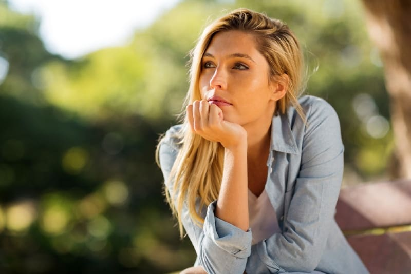 blonde woman in blue shirt sitting outdoor and thinking