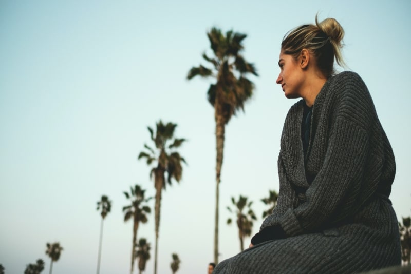 woman in gray sweater sitting near coconut trees outdoor