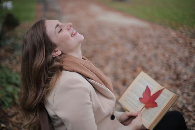 woman smiling alone with book in the hand and a maple leaf in the book