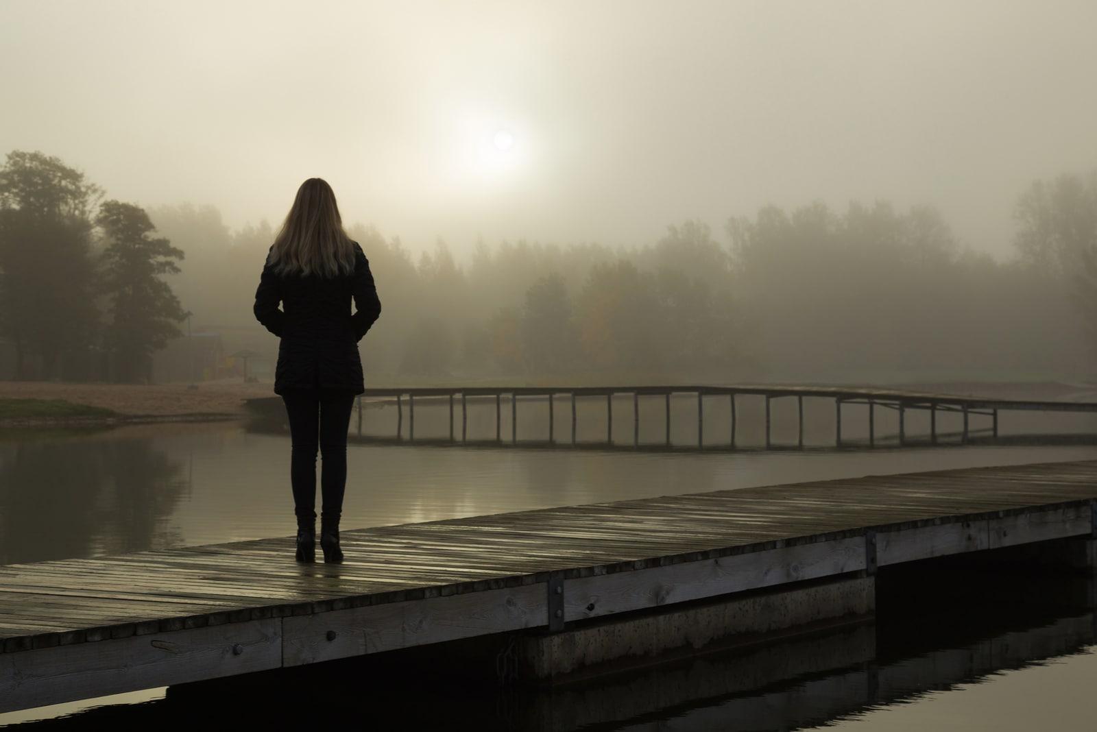 woman standing alone on lake footbridge