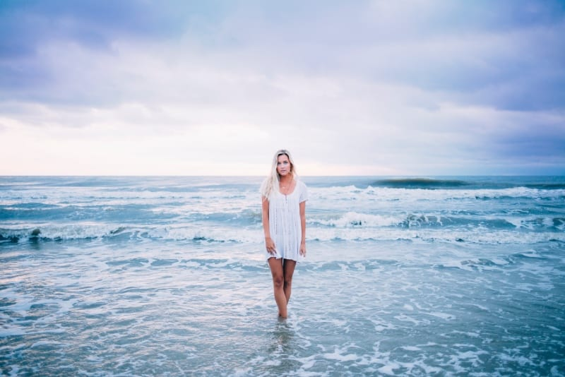woman in white dress standing in sea
