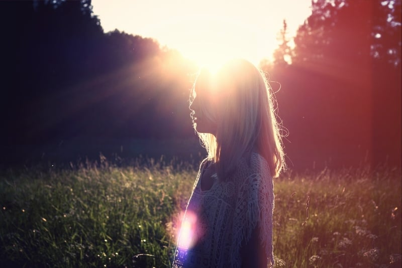 woman standing in the field during sunset