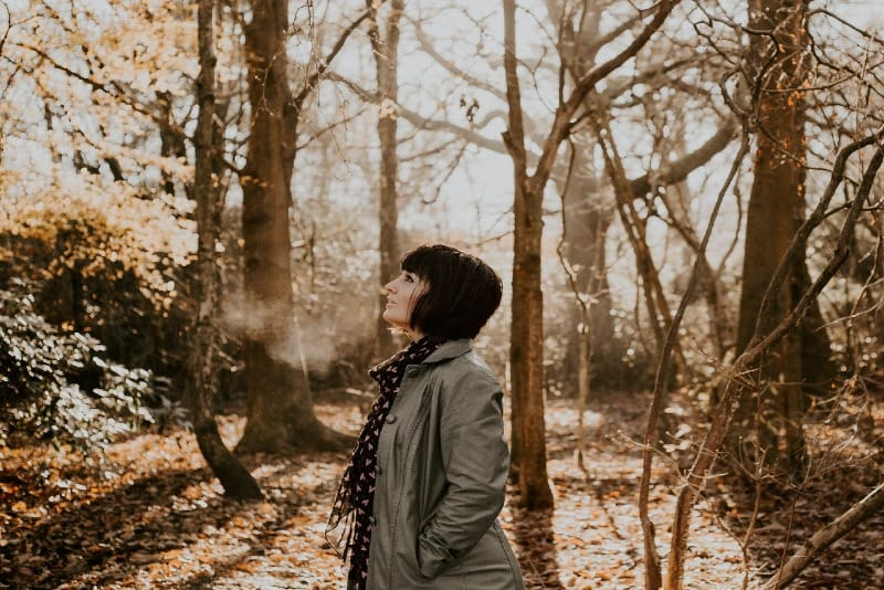 woman standing in woods looking up