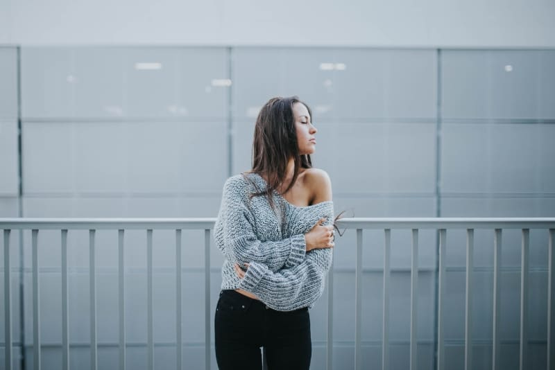 woman in gray sweater standing near white railing