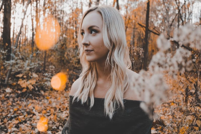 blonde woman in black off-shoulder top standing near trees