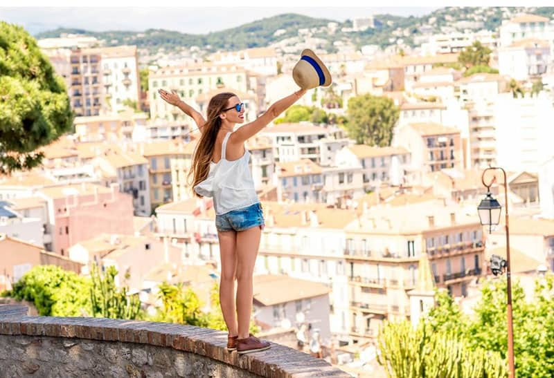 woman standing on a ledge of a building overlooking the city with arms raised for happiness