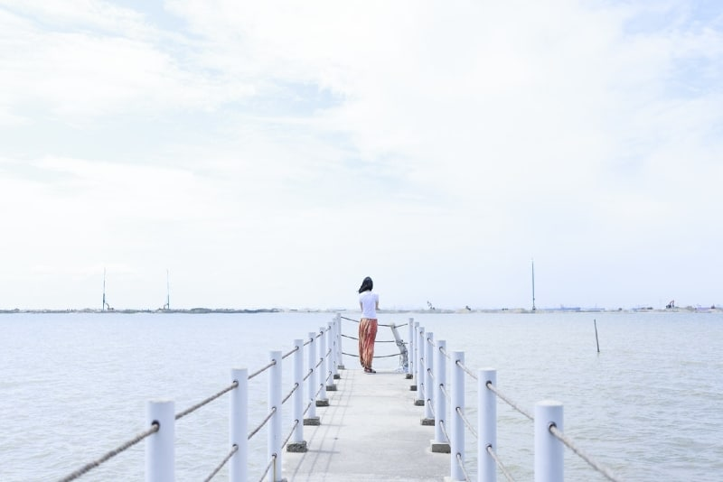 woman in white top standing on dock looking at water