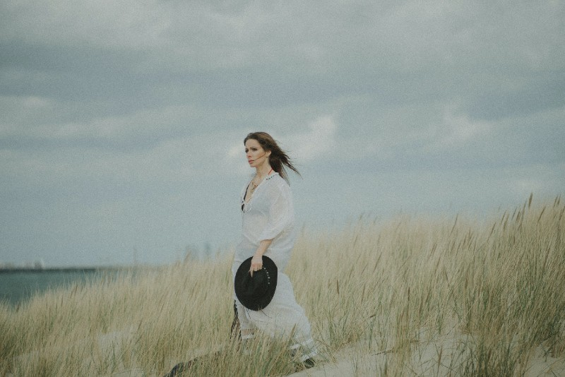 woman holding black hat standing on grass field