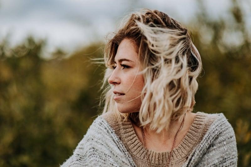 blonde woman in brown sweater standing outdoor