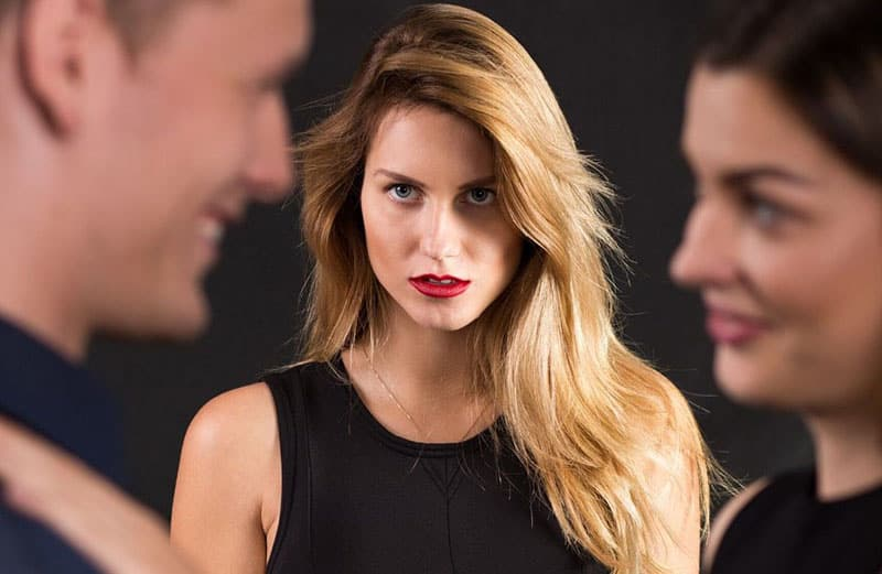 woman staring at two couple looking jealous wearing black dress