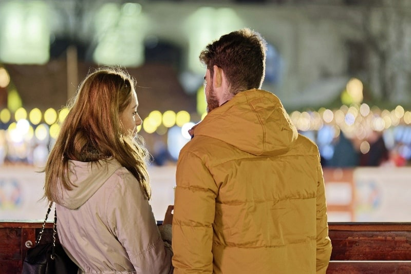 woman talking to man in yellow jacket