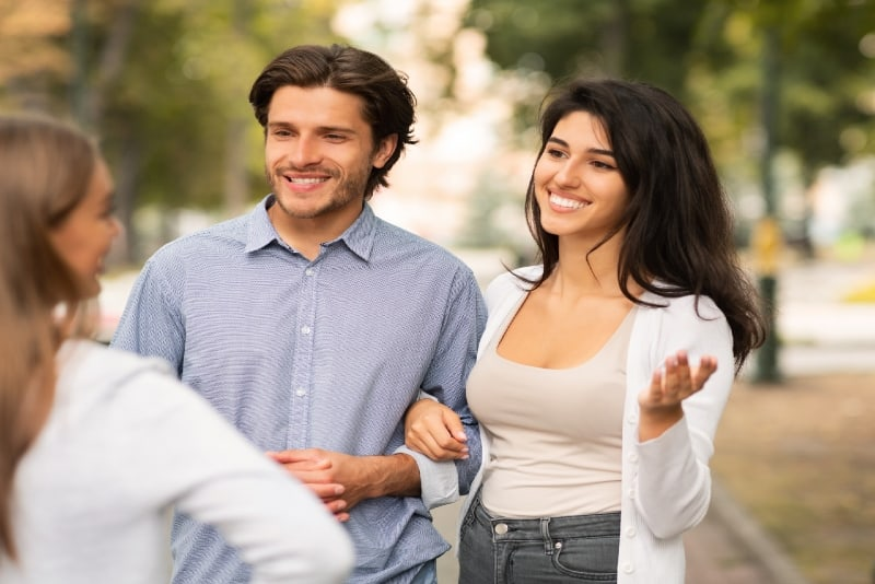 smiling woman talking to woman while holding man's hand