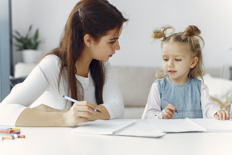 woman teaching child how to draw while sitting on floor
