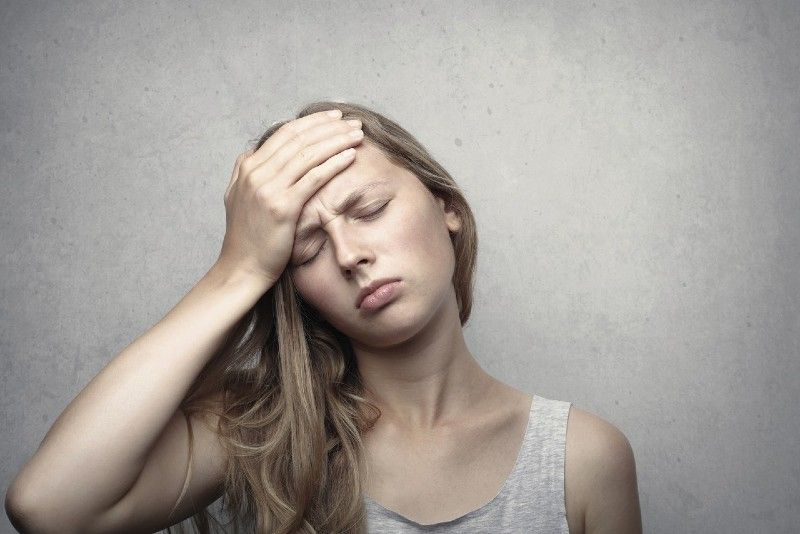 woman in gray top touching her forehead with her hand