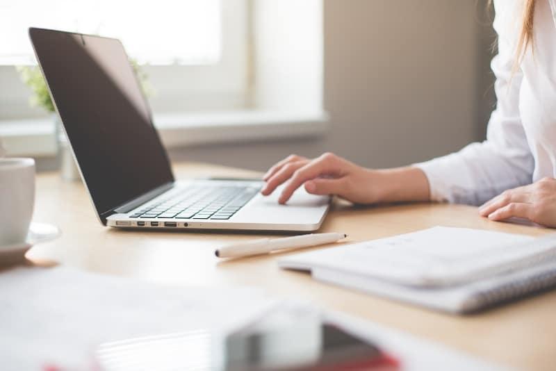 woman in white shirt using laptop