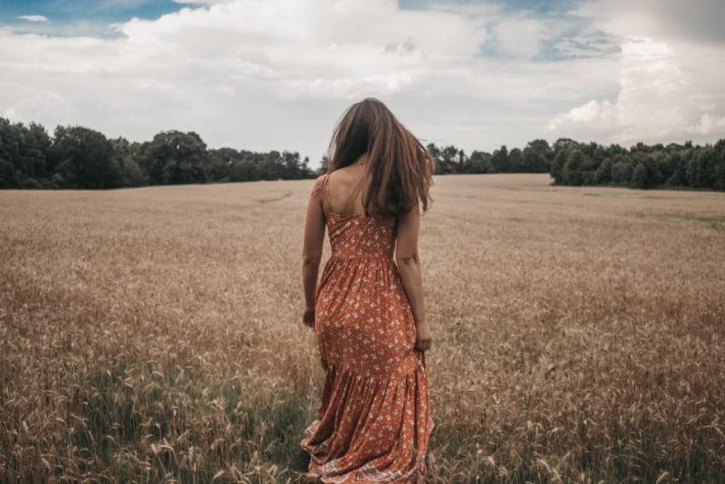 woman in orange dress walking in the field