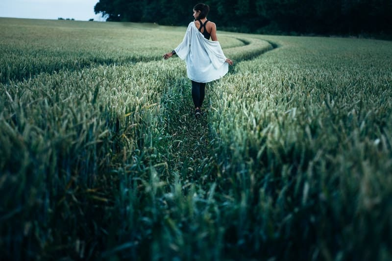 woman walking in the ricefield in a back view wearing tank top with cardigan