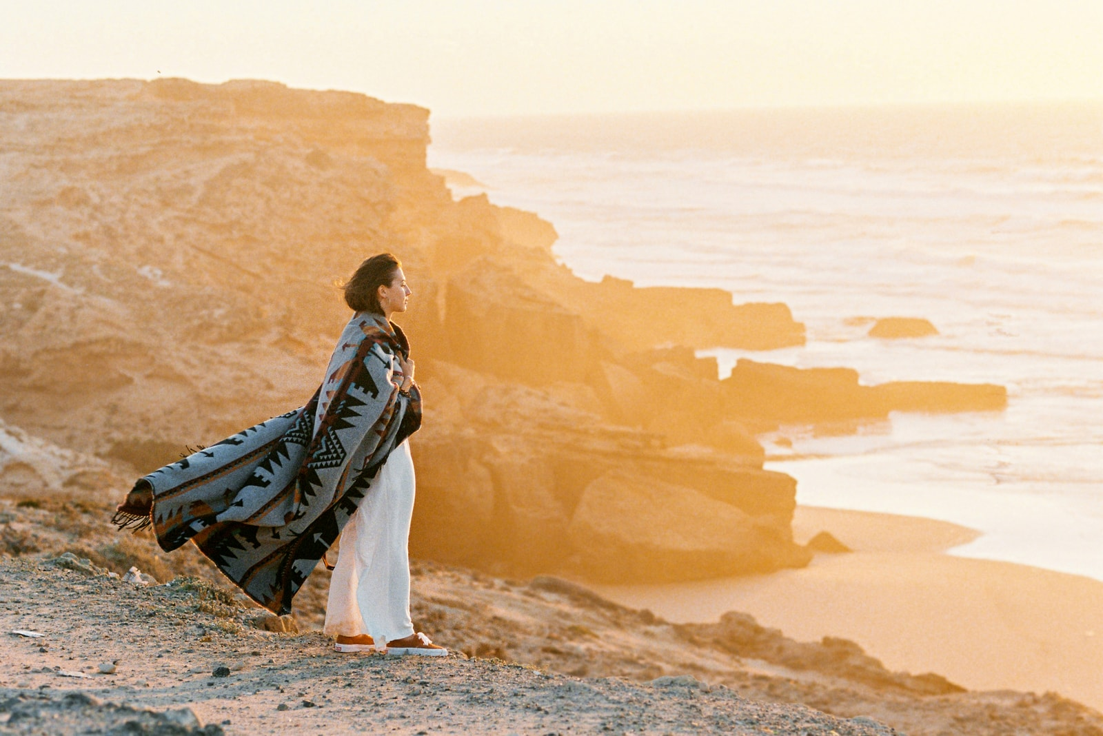 woman with flying blanket standing on cliff's edge