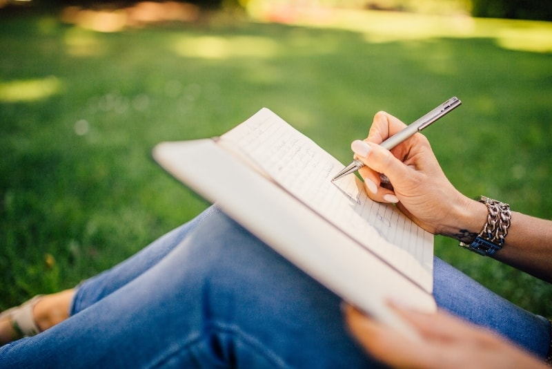 woman writing on white paper while sitting on grass