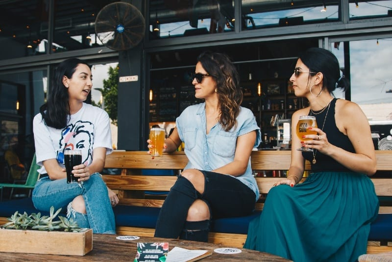 three women holding glasses of beer and talking