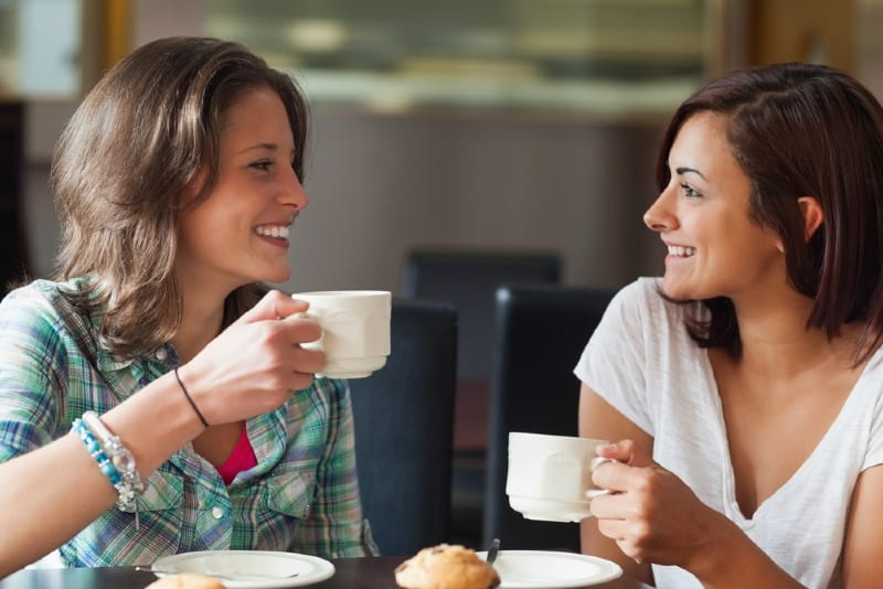 two smiling women holding white mugs and talking