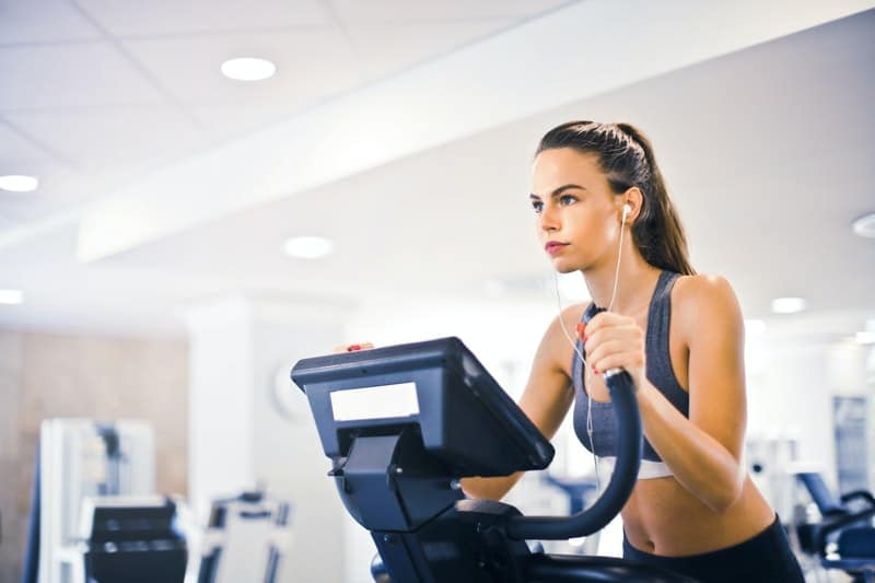 young female on a treadmill exercising wearing athletic wear and headphones