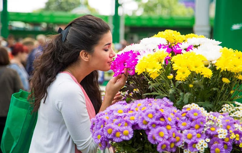 young woman buying flowers in market while smelling it