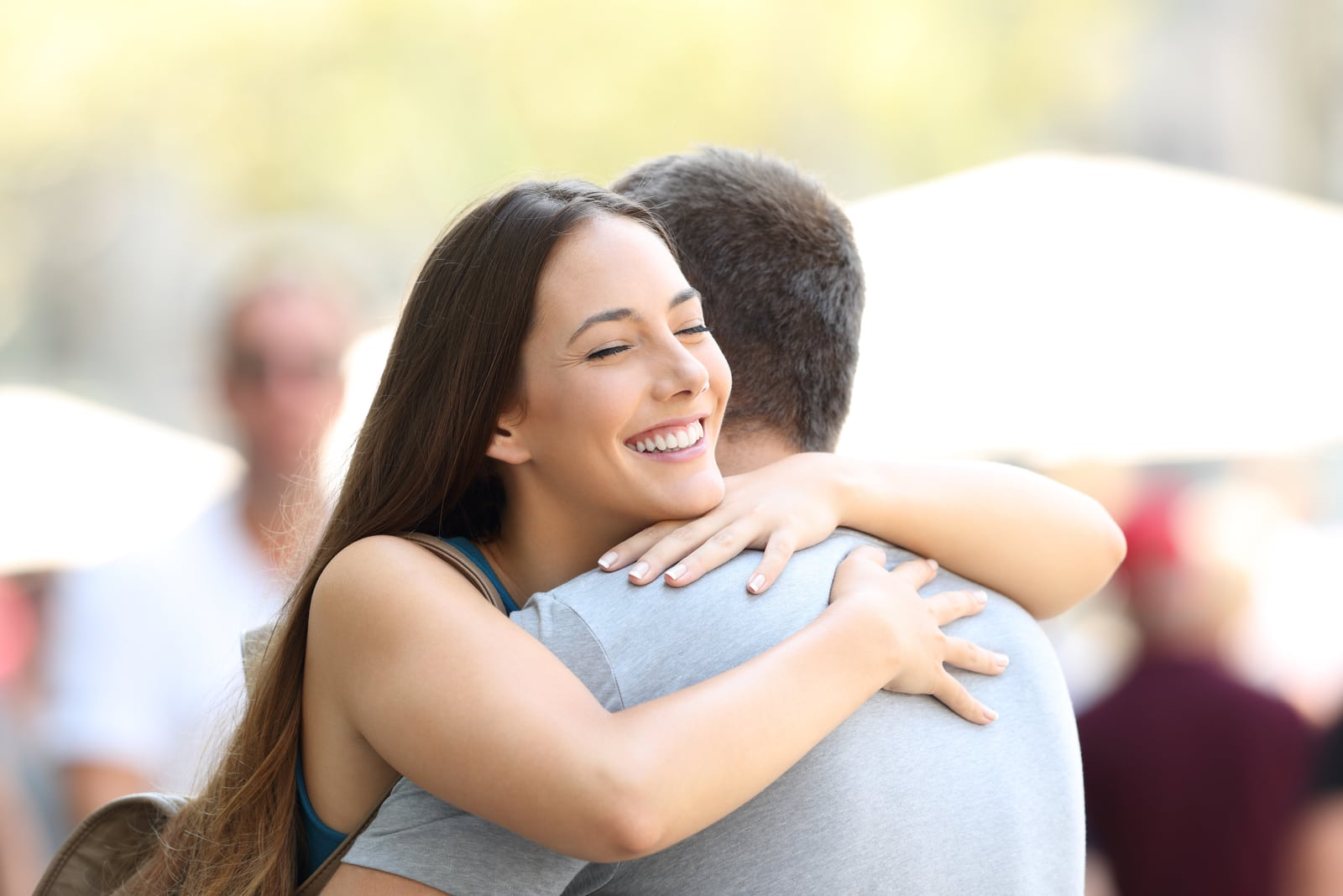 young woman smiling and hugging man outdoor