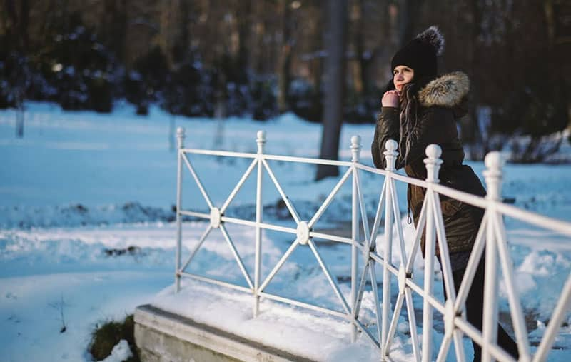 young woman standing on the bridge on a winter park