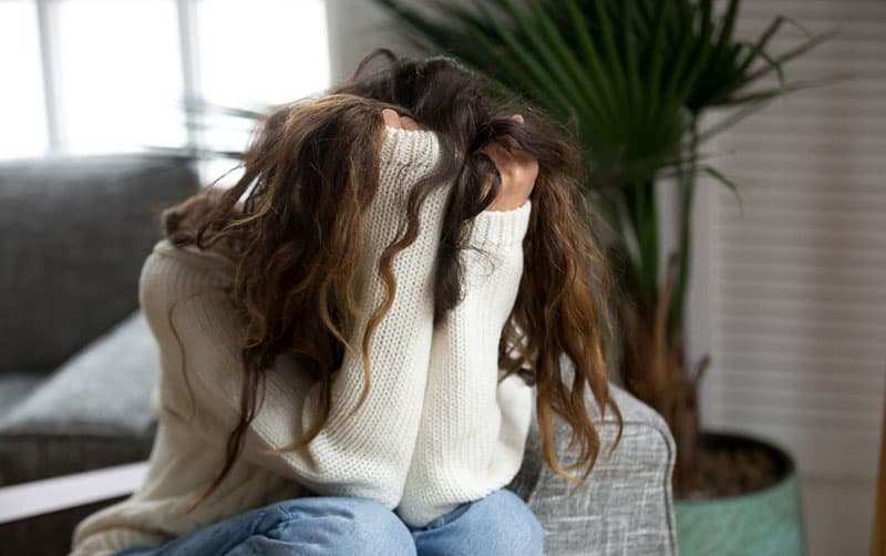 young woman suffering from a breakup crying and sitting in a couch