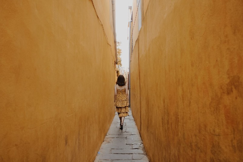 woman in yellow dress walking through pathway