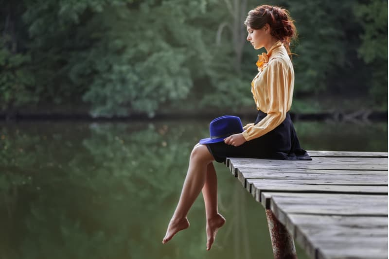 sideview of a woman sitting dreamy in the wooden platform of the lake barefooted