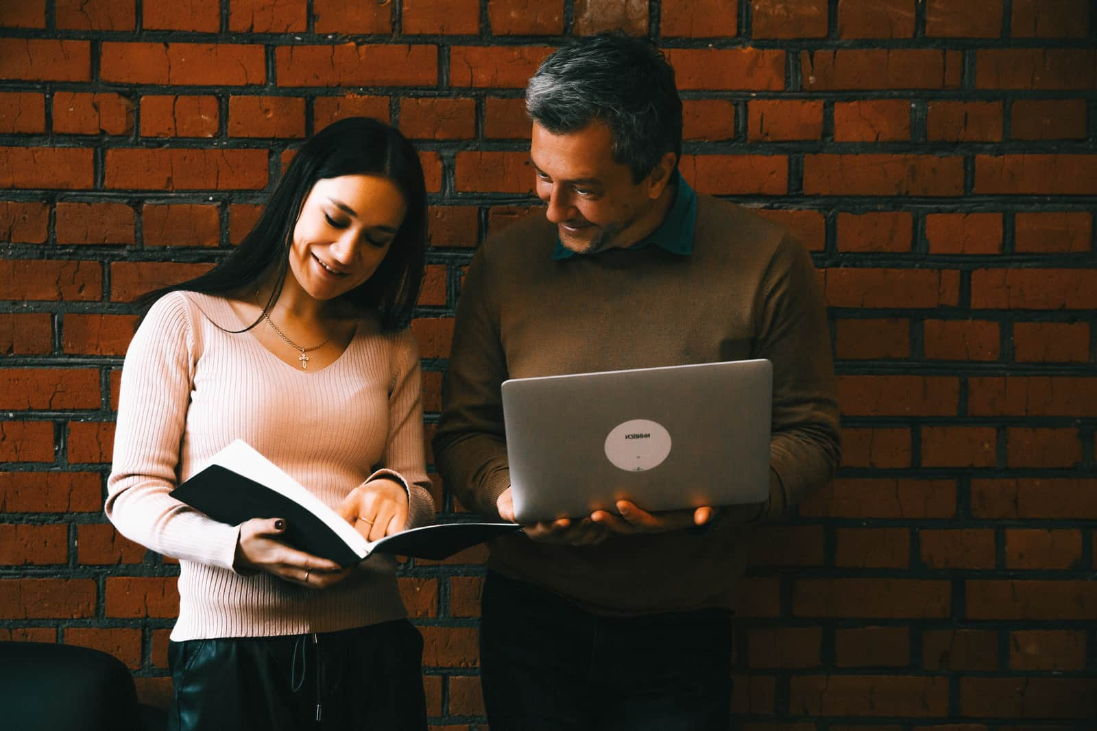 man and woman looking at notes researched on the laptop while standing near brick walls