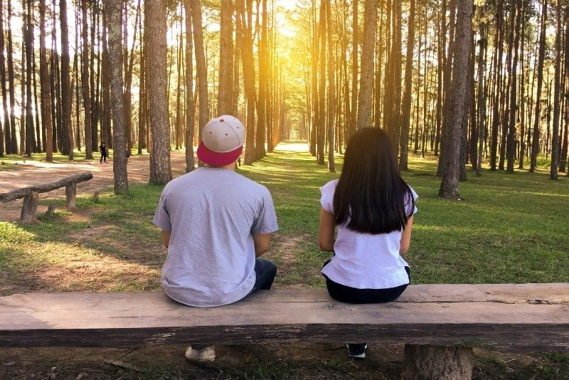 man with cap and woman sitting on bench in woods