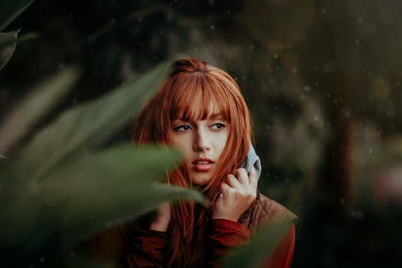 a sad red-haired woman standing outside in the rain