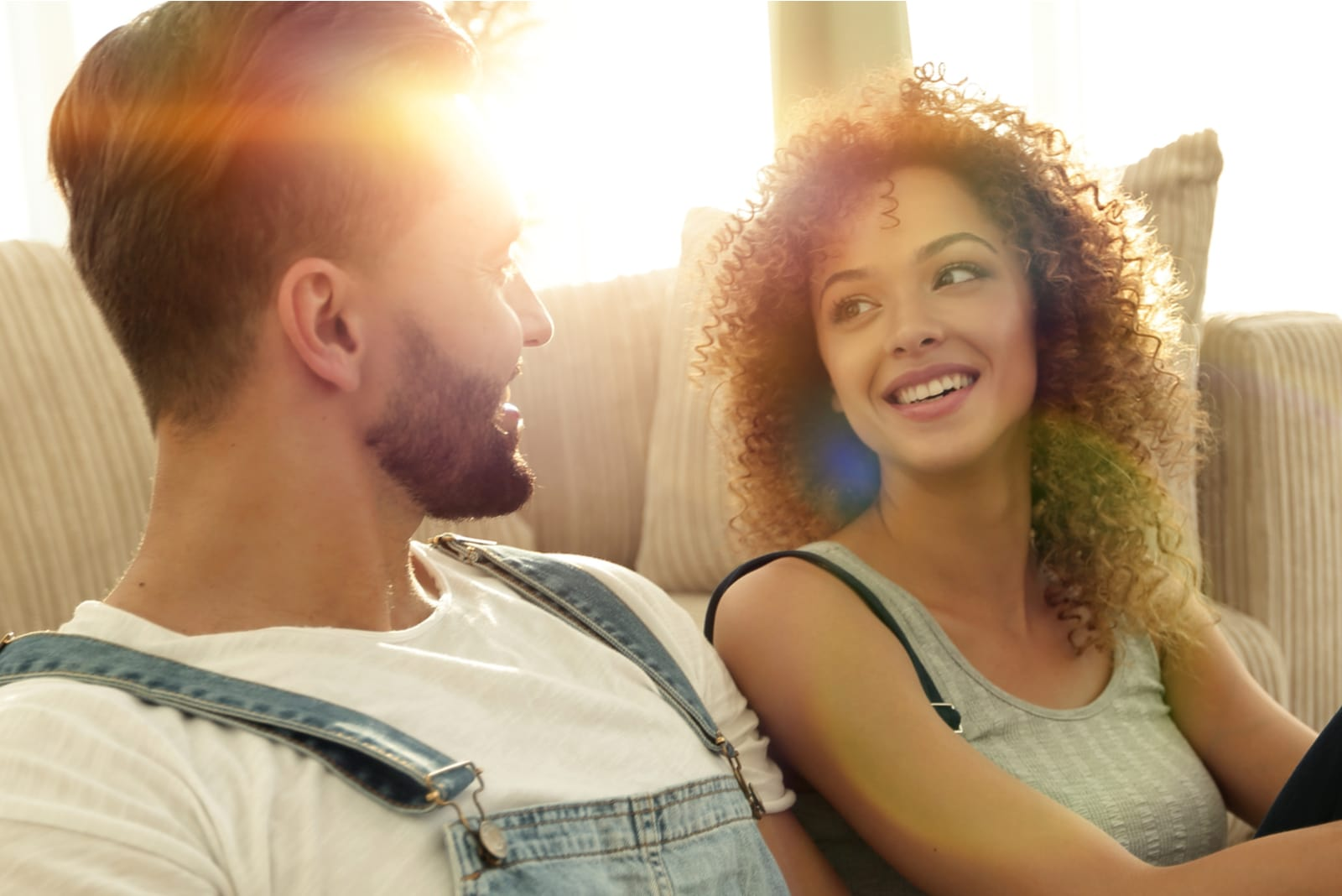 a smiling couple sits on the floor and talks