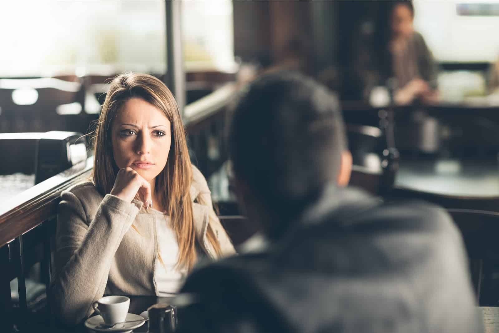 a worried brunette sitting in a cafe with a man