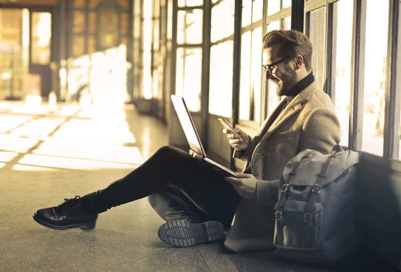 business man at the airport sitting on the floor and typing message