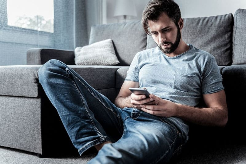 cheerles sad man looking at his cellphone and sitting on the floor near the sofa