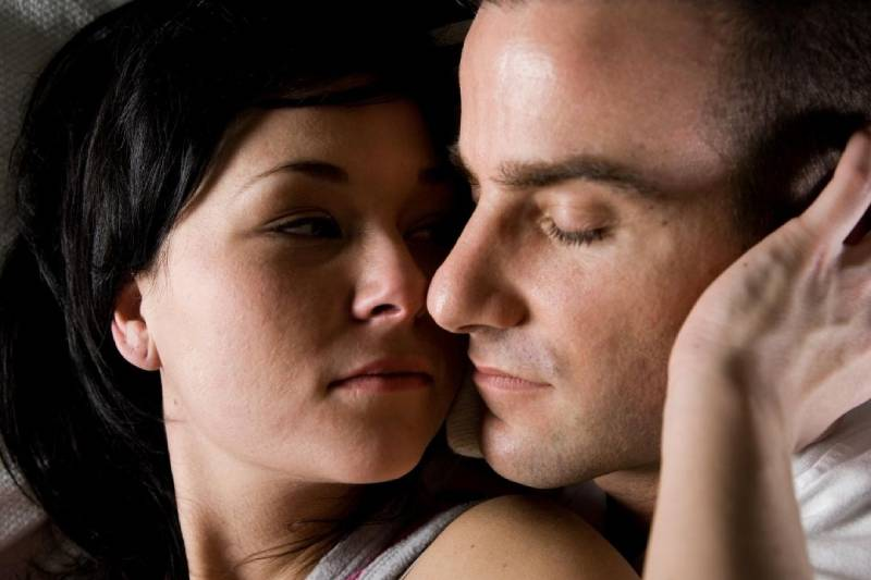 couple cuddling in bed woman touching man's face