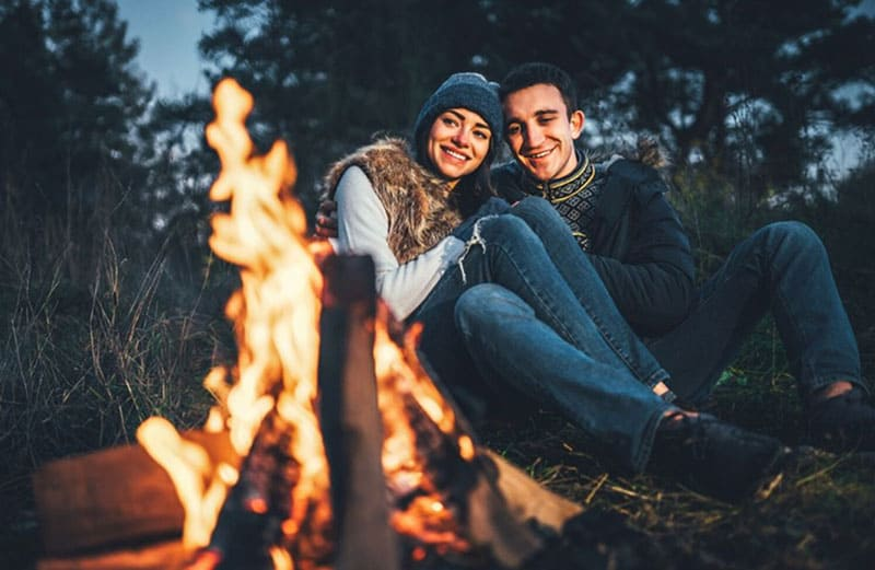 couple dating with bonfire in front of them sitting on the ground in the woods on golden hour