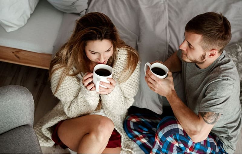couple drinking coffee in cup sitting on the floor near the bed
