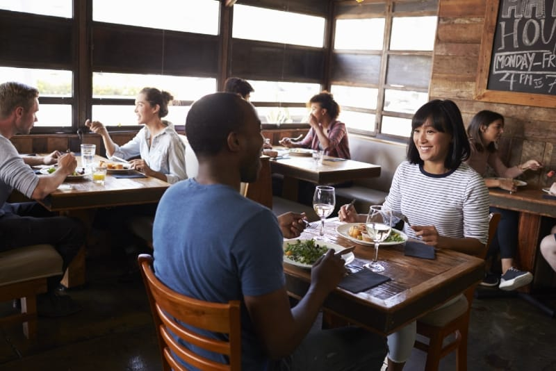 smiling woman and man eating at restaurant during daytime