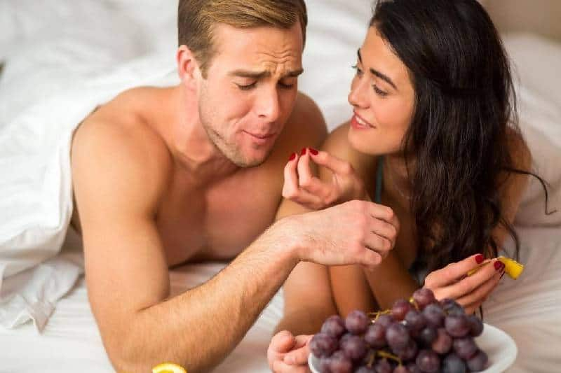 couple eating fruits on bed covering them with blanket